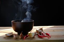Hot soup in bowl with smoke on wood table and black background stock photography