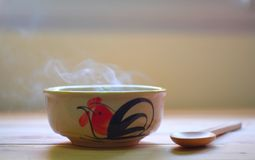 Hot soup in bowl with smoke on wood table. royalty free stock photography