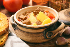 Hot soup goulash on brown wooden table. Royalty Free Stock Photos
