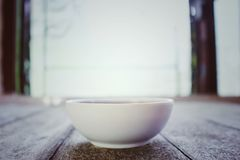 Hot soup in a white cup placed on an old wooden floor in the kitchen.  stock photo