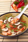 Hot-And-Sour Prawn Soup. Closeup of a bowl of hot-and-sour prawn soup with mushrooms, prawns, chili pepper and cilantro Stock Image