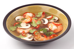 Hot-And-Sour Prawn Soup. Closeup of a bowl of hot-and-sour prawn soup with mushrooms, prawns, chili pepper and cilantro Royalty Free Stock Photography