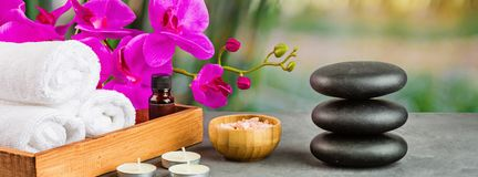 Free Hot Spa Stones Set For Massage Treatment, Orchid Flower, Towels, Candles And Sea Salt On Green Background With Bamboo. Elegant And Royalty Free Stock Photography - 166350717