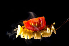 Hot spaghetti pasta with basil and greenery swirl on a fork with a piece of cherry tomatoes and steam isolated on black Stock Photo