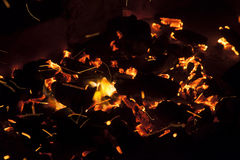 Hot sparking live-coals burning in a barbecue Royalty Free Stock Photos