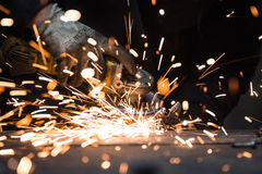 Hot sparks from grinding steel material. On a table Royalty Free Stock Image