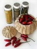 Hot Spice. A basket with red chili peppers and three flasks of spices over white background Stock Photo