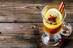 Hot spiced Apple cider Toddy with lemon, honey and cinnamon stick in glass. On wooden background royalty free stock photo