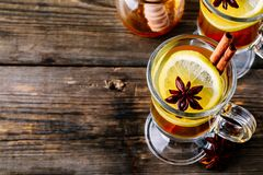 Hot spiced Apple cider Toddy with lemon, honey and cinnamon stick in glass. On wooden background stock photography