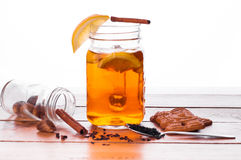 Hot spiced tea in jar on wooden table Stock Photos