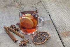 Hot Spiced Wine. Glass of hot spiced wine with cinnamon oranges and star anise on rustic wooden table Stock Images