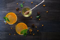 Hot spicy beverage with sea buckthorn in glass cups  with fresh raw sea buckthorn berries and cinnamon sticks, anise stars and hon. Ey on a dark kitchen table Royalty Free Stock Photography