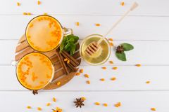 Hot spicy beverage with sea buckthorn in glass cups  with fresh raw sea buckthorn berries and cinnamon sticks, anise stars and hon. Ey on a white kitchen table Royalty Free Stock Photography