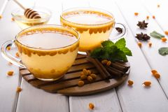 Hot spicy beverage with sea buckthorn in glass cups  with fresh raw sea buckthorn berries. And cinnamon sticks, anise stars and honey on a white kitchen table Stock Photos