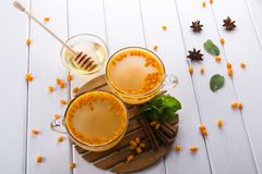 Hot spicy beverage with sea buckthorn in glass cups  with fresh raw sea buckthorn berries. And cinnamon sticks, anise stars and honey on a white kitchen table Royalty Free Stock Photography