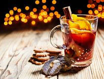 Hot spicy Christmas gluhwein served with cookies. Hot spicy Christmas gluhwein, or mulled red wine with sugar and spices, served with cookies on rustic wood with Stock Image