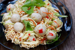 Hot spicy fish balls noodles. Hot and sour red chili instant noodle served with fish balls and vegetables Stock Photos