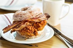 Hot spicy fried chicken and bacon sandwich in a donut. With a cup of coffee royalty free stock photos