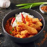 Hot Spicy Fried Shrimps with Curry and Rice. In Black Bowl. Crispy Prawns in Breadcrumbs with Red Peppres, Tomatoes, Chilli Sauce, Sesame, Green Onion and Herbs royalty free stock photo