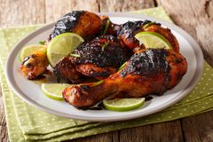 Hot spicy grilled chicken drumstick with lime and green onion cl. Ose-up on a plate on a table. horizontal Stock Photo