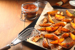 Hot Spicy Potato Wedges on Tray with Slotted Ladle Royalty Free Stock Images