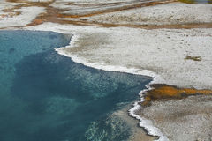 Hot spring with clear, blue water and white lime rim. Royalty Free Stock Photo