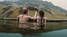 Hot spring geothermal spa in Iceland. Two traveling woman relaxing in hot pool with beautiful landscape on mountain. Young women enjoying bathing, relaxed in a stock footage