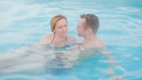 Hot spring geothermal spa. Romantic couple in love relaxing in hot pool. Young woman and man enjoying bathing relaxed in a blue water lagoon tourist attraction stock footage