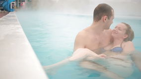 Hot spring geothermal spa. Romantic couple in love relaxing in hot pool. Young woman and man enjoying bathing relaxed in a blue water lagoon tourist attraction stock video