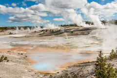 Hot spring pools at Norris Basin with blue and orange colors and steam geysers Stock Photo