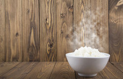 Hot Steamed Rice in a White Bowl with White Vapor on wooden background Stock Photos