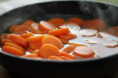 Hot steaming carrots in frying pan Royalty Free Stock Photo