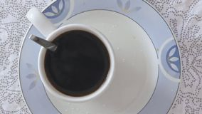 Hot steaming coffee in coffee cup. On the kitchen table in slow motion video footage filmed from above stock video