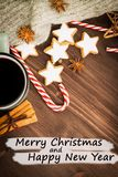 Hot steaming cup of glint wine with spices, anise, cinnamon, cookies in a shape of star, red candies, pepper on wooden background. With text Merry Christmas and stock photo