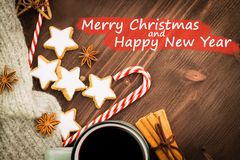 Hot steaming cup of glint wine with spices, anise, cinnamon, cookies in a shape of star, red candies, pepper on wooden background. With text Merry Christmas and stock photos