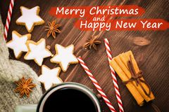 Hot steaming cup of glint wine with spices, anise, cinnamon, cookies in a shape of star, red candies, pepper on wooden background. With text Merry Christmas and royalty free stock photography