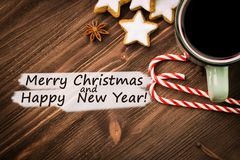 Hot steaming cup of glint wine with spices, anise, cookies in a shape of star, red candies, pepper on wooden background with text. Merry Christmas and Happy New stock images