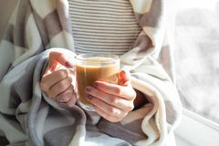 Hot steaming drink in woman`s hands. Female covered in throw bla. Nket sits by the window with cup of hot cocoa stock photography