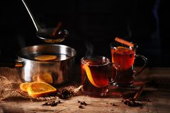 Hot steaming mulled wine cooked  in a pot and served in glass mu Stock Photography