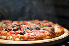 Hot Steaming Pizza in Oven. Hot supreme thin crust pizza cooking in oven with steam and smoke Stock Image