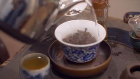 Hot steaming water pouring into beautiful porcelain bowl with lo. Hot steaming water pouring from shiny metallic kettle into beautiful porcelain bowl with loose stock video