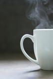 Hot Steaming White Ceramic Mug. A white ceramic mug full of a hot steaming liquid. Coffee? Tea? Herbs? Cocoa? Milk? Lemon water? It for you to decide Stock Photo