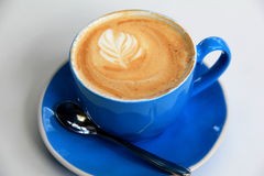 Hot and steamy cappuccino in bright blue cup Stock Photos