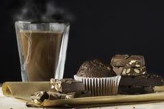 Hot steamy chocolate, stack of dark chocolate, chocolate muffin. Dark background, copy space Royalty Free Stock Photo