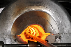 Hot steel. A hot steel bar exiting from a forge Stock Photography