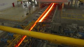 Hot steel on conveyor in steel mill. Hot steel on conveyor belt in a steel mill . The steel block in the process of changing its form stock video footage