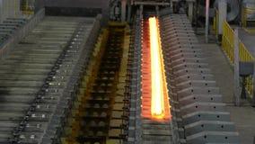 Hot steel on conveyor in steel mill. Hot steel on conveyor belt in a steel mill . The rails are directed to its bend stock footage