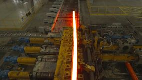 Hot steel on conveyor in steel mill. Hot steel on conveyor belt in a steel mill . The steel block in the process of changing its form stock footage