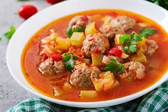 Hot stew tomato soup with meatballs and vegetables. Closeup in a bowl on the table. Albondigas soup, spanish and mexican food stock photo