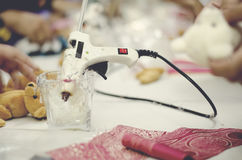 Hot stick glue gun on cup. red fabrick and doll on white table Royalty Free Stock Photo